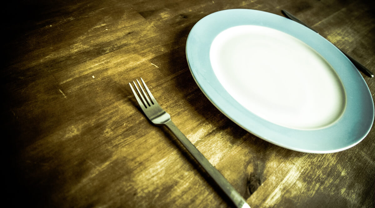 Blue-Rimmed Plate and Utensils on a Wooden Table
