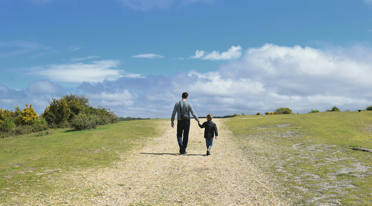 Father and Son Walking Down a Footpath on a Sunny Day