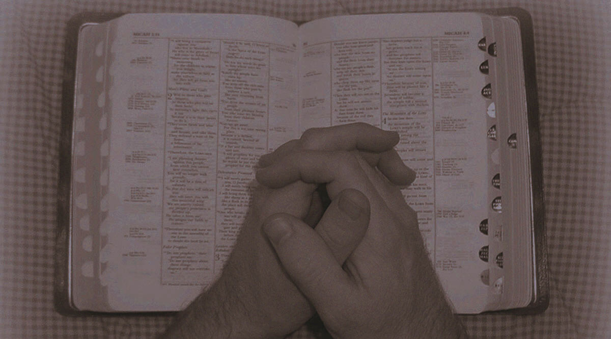 Folded Hands on a Bible on a Sheet