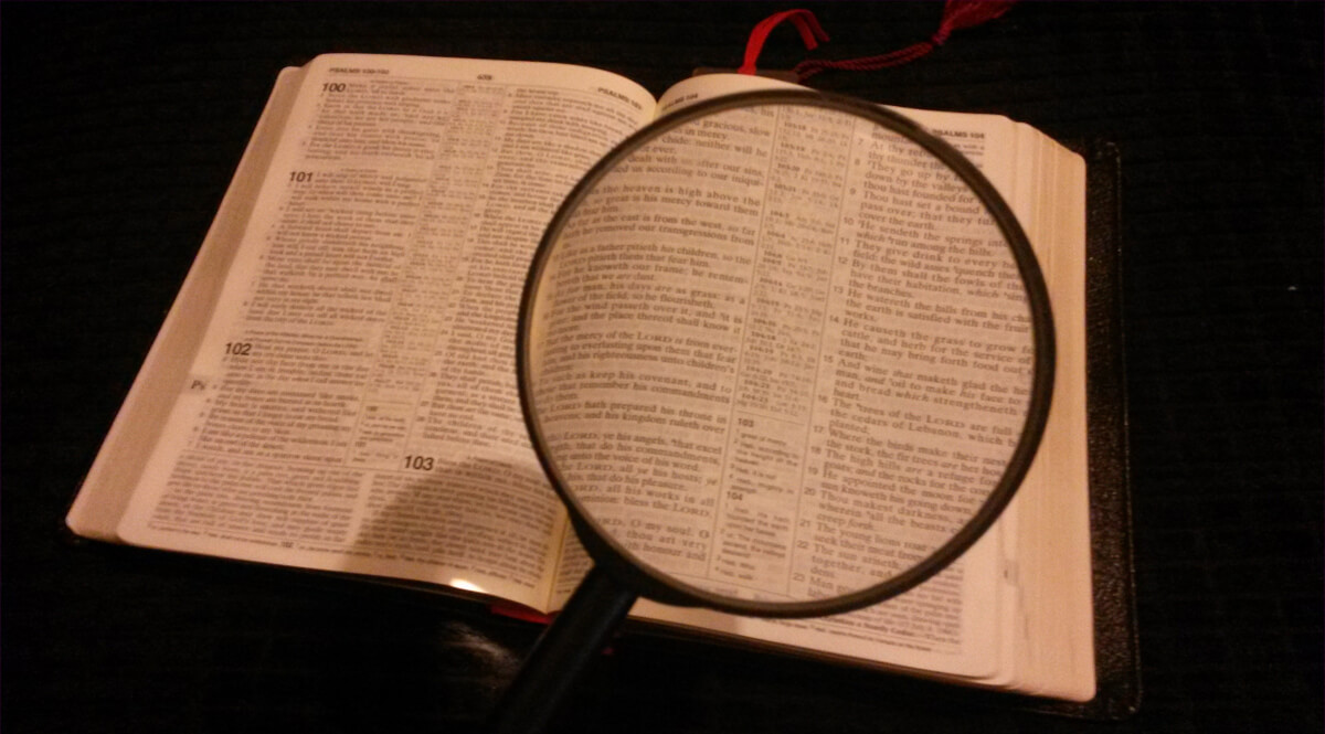 Magnifying Glass Over Bible Open to Psalms 100 to 104