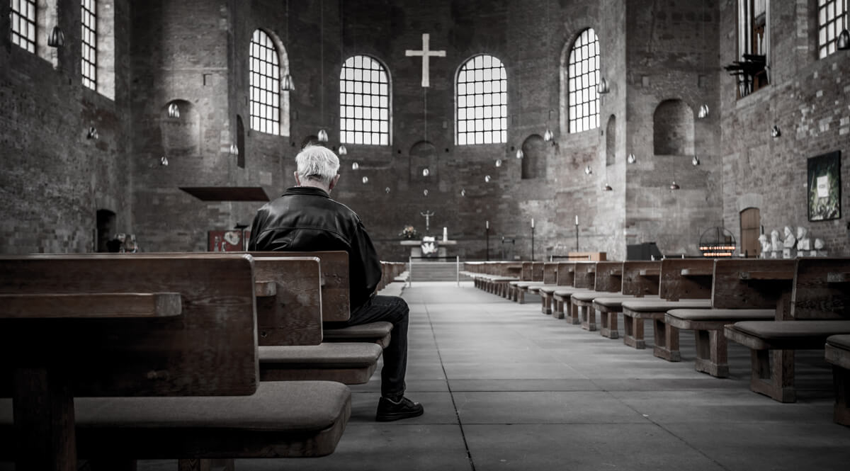 Man Sitting in an Empty Cathedral