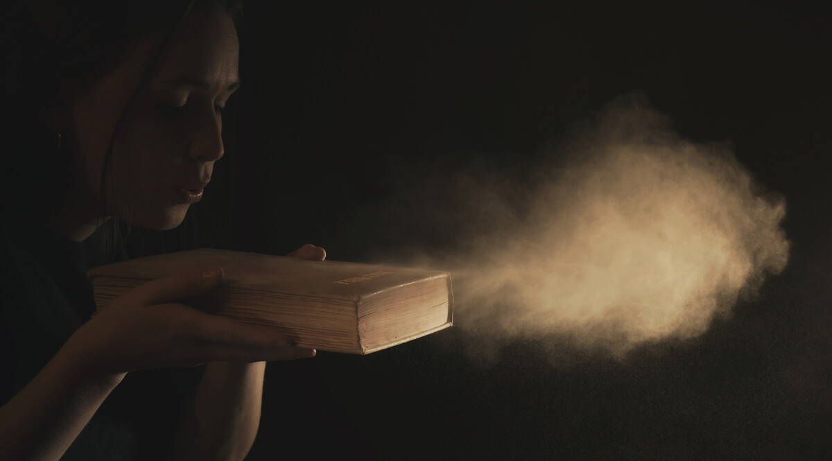 Woman Blowing Dust Off the Cover of an Old Bible
